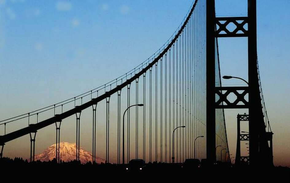 Mount Rainier peers through the Tacoma Narrows Bridge at sunset on July 5, 2001.