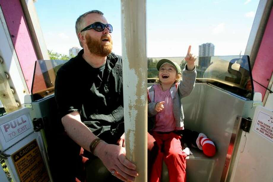 An excited Sharky McGarry rides the Ferris wheel at Seattle Center's Fun Forest with his dad, Ted Mundy, on June 10, 2007. (Dan DeLong/Seattlepi.com file) Photo: P-I File