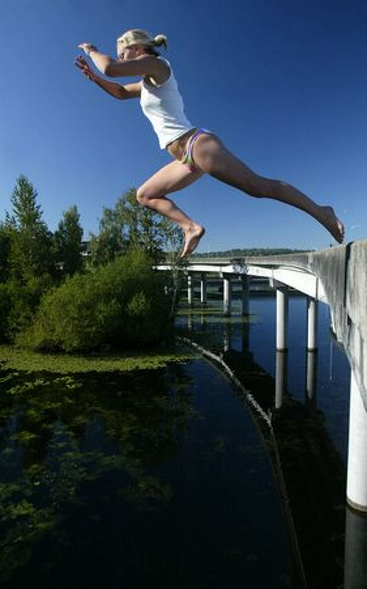 Alex Merrick takes a flying leap off a closed and unused section the 520 Bridge into the cool water of the Washington Park Arboretum below on Monday August 8, 2005 in Seattle. The unused ramp is a popular spot where Seattelites have plunged into the water below for many years.