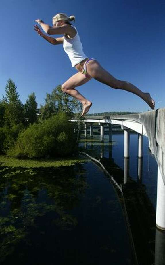 Alex Merrick takes a flying leap into the cool water of the Washington Park Arboretum on Aug. 8, 2005. The unused ramp has been popular with summer jumpers for decades. Until 1936, the current site of the ramps to nowhere was home to the Miller Street Dump. Read more here from Historylink.org's John Caldbick. Photo: JOSHUA TRUJILLO, SEATTLEPI.COM FILE