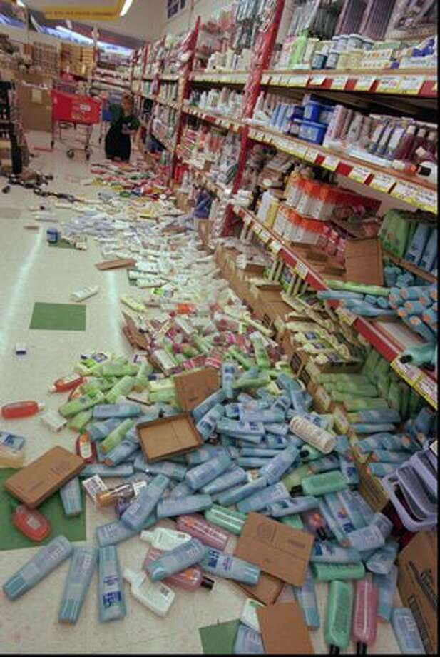 Tami Farmer cleans up the floor at the Monroe Grocery Outlet store on May 3, 1996 after a 5.4 earthquake hit Western Washington. (AP Photo/Barry Sweet/seattlepi.com file) Photo: P-I File