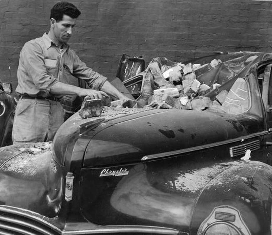 A man inspects his car after the April 13, 1949 Seattle earthquake. (seattlepi.com file) Photo: P-I File