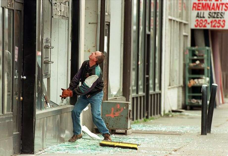 "The Feb. 28, 2001 photo caption read: Wayne VanDire cleans up broken glass in front of the Encore Restaurant Equipment on 1st Avenue South where he works. He's from L.A., been in Seattle 15 years, ands said ""this is the worst earthquake I've been in."" During the earthquake, a 900 pound grill moved from a wall into the middle of the store. (seattlepi.com file) Photo: P-I File"