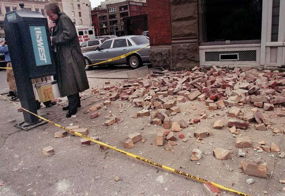 The Feb. 28, 2001 photo caption read: A man crosses the police line to make a phone call on Second Avenue South in the Pioneer Square area of Seattle where bricks fell near the Cafe Hue. (seattlepi.com file) Photo: P-I File
