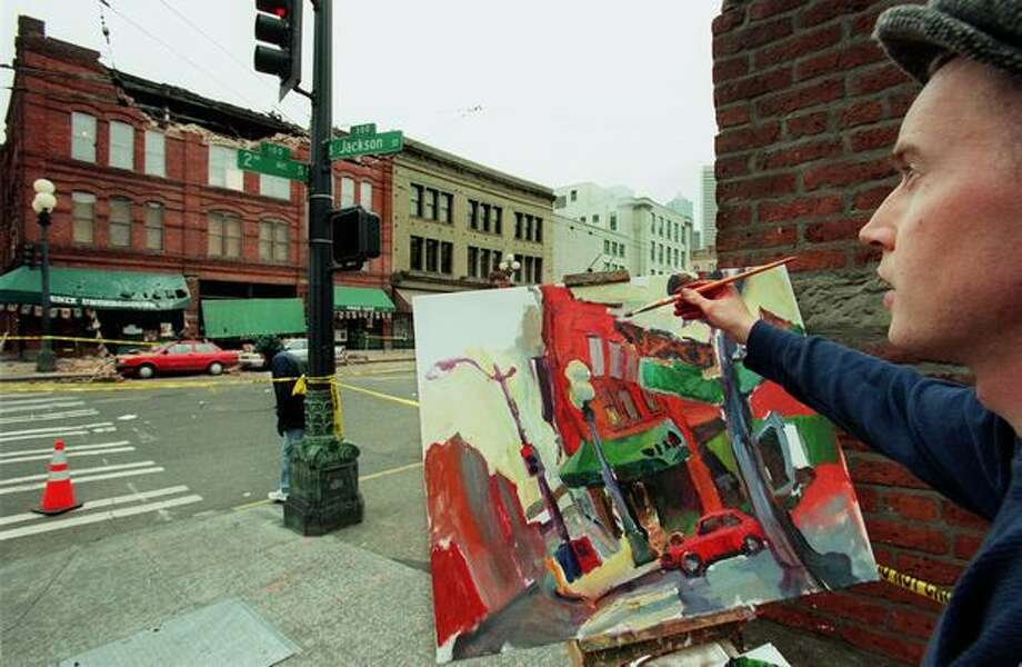 Seattle artist Ethan Harrington paints an earthquake scene featuring the Fenix Underground in Pioneer Square on March 1, 2001. (seattlepi.com file) Photo: P-I File