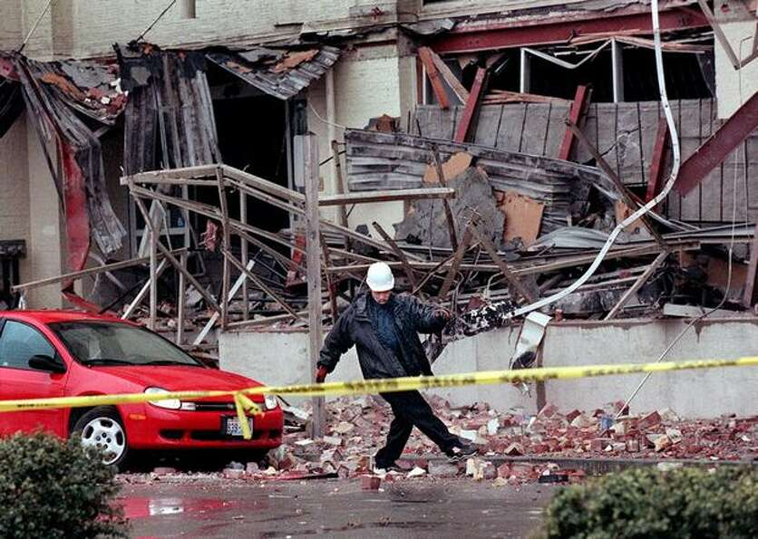A tow truck driver kicks bricks to the side from an earthquake-damaged Sodo building in Seattle befo