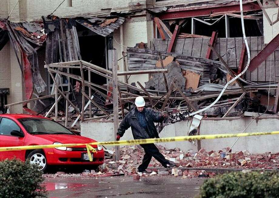 A tow truck driver kicks bricks to the side from an earthquake-damaged Sodo building in Seattle before towing away a car that was damaged there during the Feb. 28, 2001 earthquake. (seattlepi.com file) Photo: P-I File