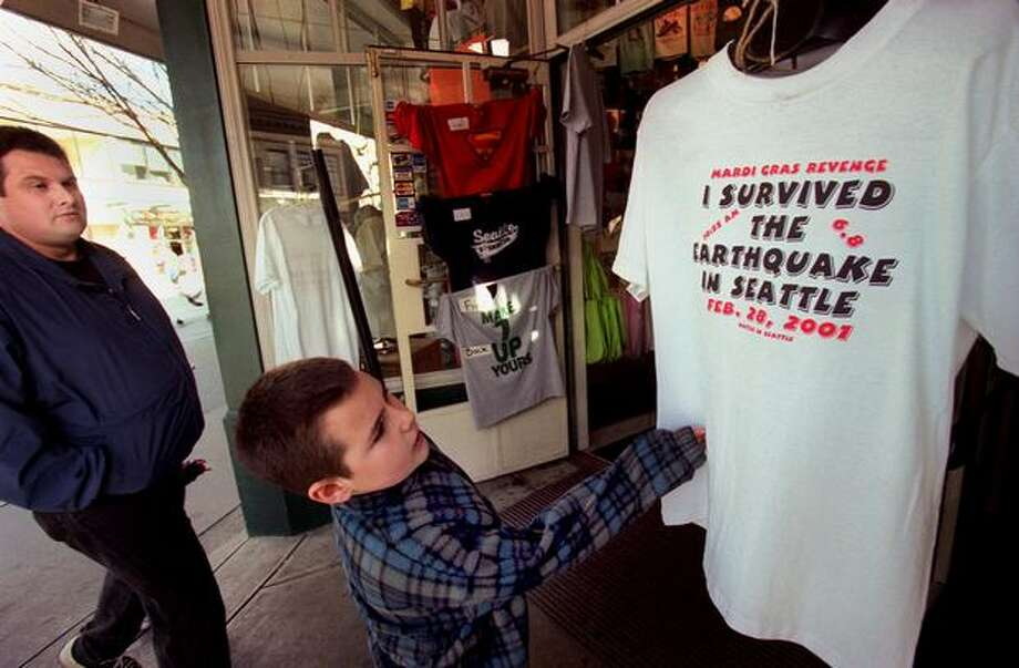 The March 2001 photo caption read: 8-year-old David Fleck of Olympia takes a look at an earthquake T-shirt while his father, Jeff Fleck, follows him into The Seattle Shirt Company. (seattlepi.com file) Photo: P-I File
