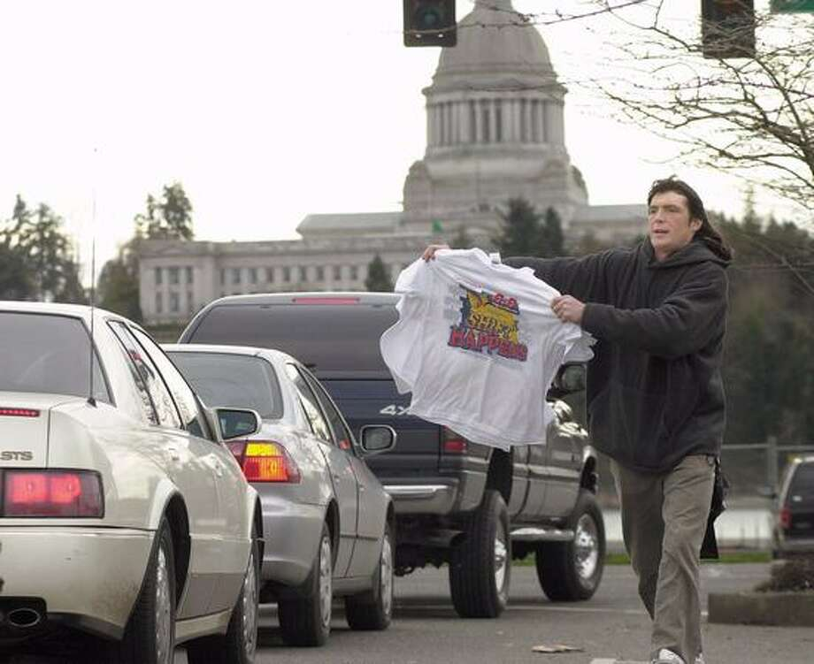 The March 2001 photo caption read: Jerry Mosher of Seattle is one of a crew of about a dozen entrepreneurs that hit the streets of Olympia, Wash., Sunday, March 4, 2001, hawking souvenir earthquake T-shirts. Engineers found more damage at the state Capitol, rear, from Wednesday's 6.8-magnitude quake, delaying lawmakers' return to the building anytime soon, officials said Saturday. (AP Photo/Louie Balukoff/seattlepi.com file) Photo: P-I File