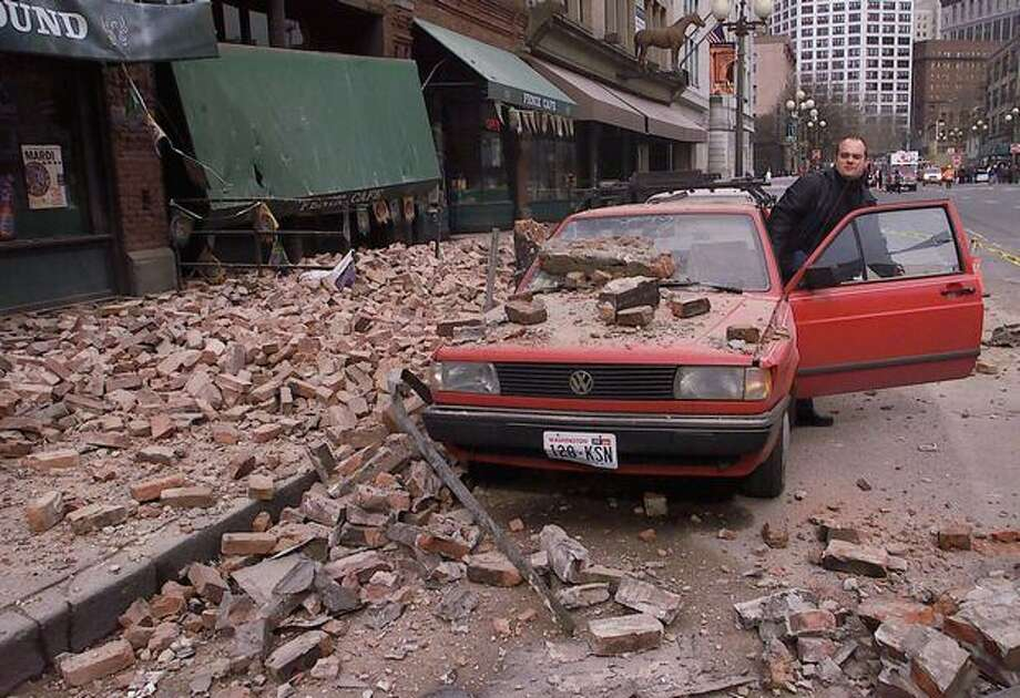 Paul Riek checks to see if his car starts after rubble from a nearby building fell on it following the Feb. 28, 2001 earthquake in downtown Seattle. (AP Photo/Stevan Morgain/seattlepi.com file) Photo: P-I File