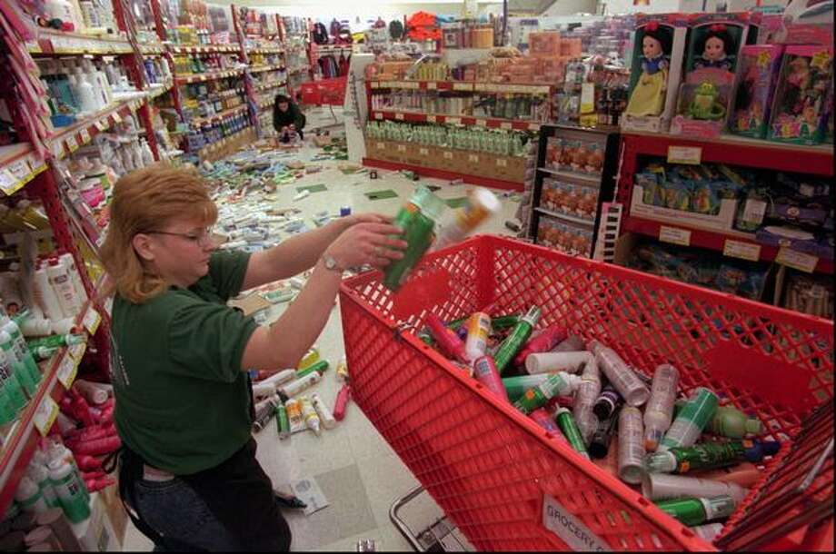 Tami Farmer cleans up the floor at the Monroe Grocery Outlet store on May 3, 1996 after a 5.4 earthquake hit Western Washington. It was the strongest earthquake to hit the state in 15 years and the Seattle Mariners baseball game in Seattle was suspended in the seventh inning. There were no reports of serious injuries. (AP Photo/Barry Sweet/seattlepi.com file) Photo: P-I File
