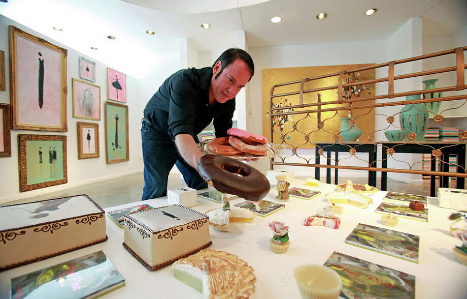"Franco Mondini-Ruiz places a giant doughnut from Panifico Bake Shop on one of his creations as he works in the gallery/studio in Alamo Heights where his ""Ginormous"" exhibit is displayed for Contemporary Art Month. TOM REEL / EXPRESS-NEWS / © 2011 San Antonio Express-News"