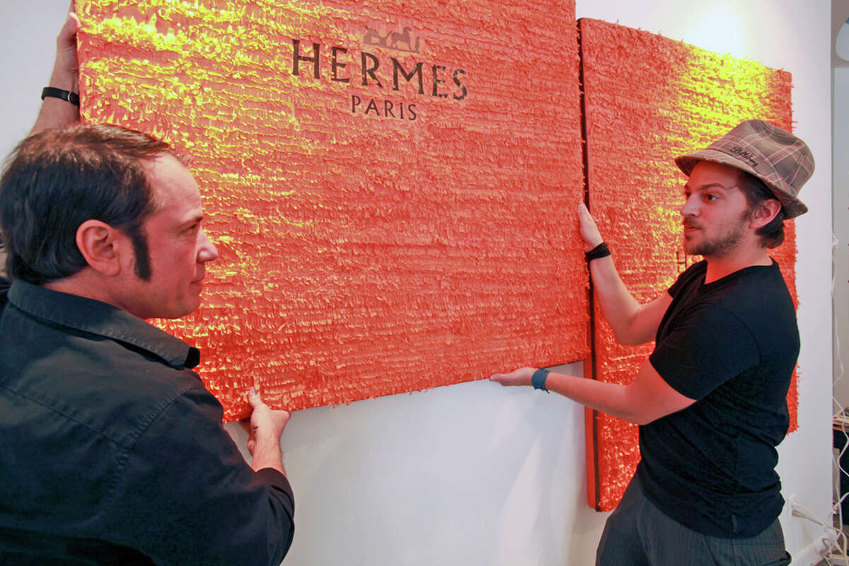 Mondini-Ruiz (left) gets a hand from Ethan Moore in positioning his pinata-style paintings with the Hermes logo. Mondini-Ruiz is creating new pieces to replace those that have been sold during the CAM exhibit. TOM REEL / EXPRESS-NEWS