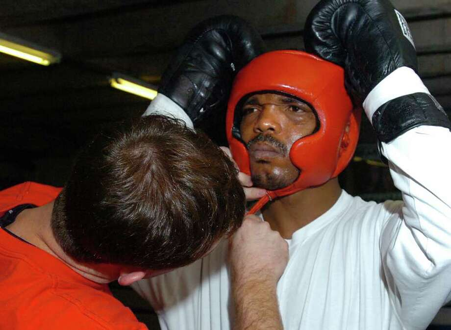 Bobby Benton gears up Chris Henry for a practice match at the Main Boxing Gym in Houston during a workout in January, 2009. Guiseppe Barranco/The Enterprise / Beaumont