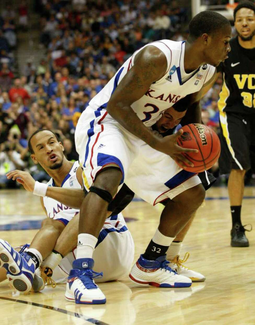 Kansas guard Josh Selby (32) gets tangled up with Virginia Commonwealth guard Joey Rodriguez (12) and Kansas guard Travis Releford (24) during the first half of the NCAA Southwest Regional final in San Antonio, Texas on Sunday, March 27, 2011. (Jerry Lara/glara@express-news.net)