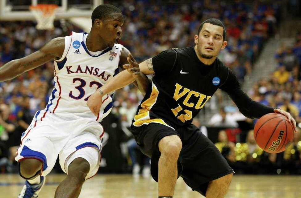 Virginia Commonwealth guard Joey Rodriguez (12) drives around Kansas guard Josh Selby (32) during the first half of the NCAA Southwest Regional final in San Antonio, Texas on Sunday, March 27, 2011. (Jerry Lara/glara@express-news.net)