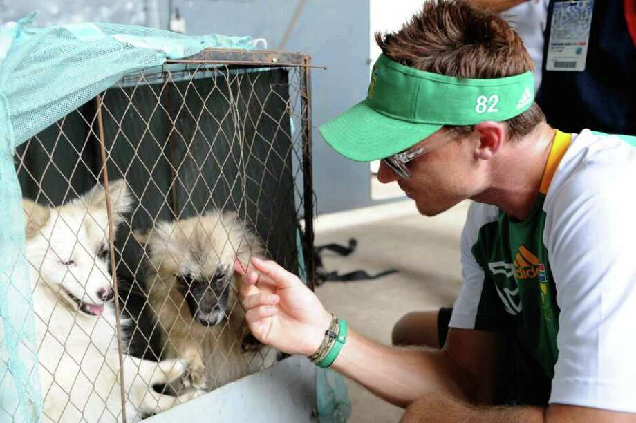 Dale Steyn of South Africa plays with a puppy during a South Africa nets session at SBNCS Stadium in Dhaka, Bangladesh. Photo: Gallo Image, Getty Images / 2011 Getty Images