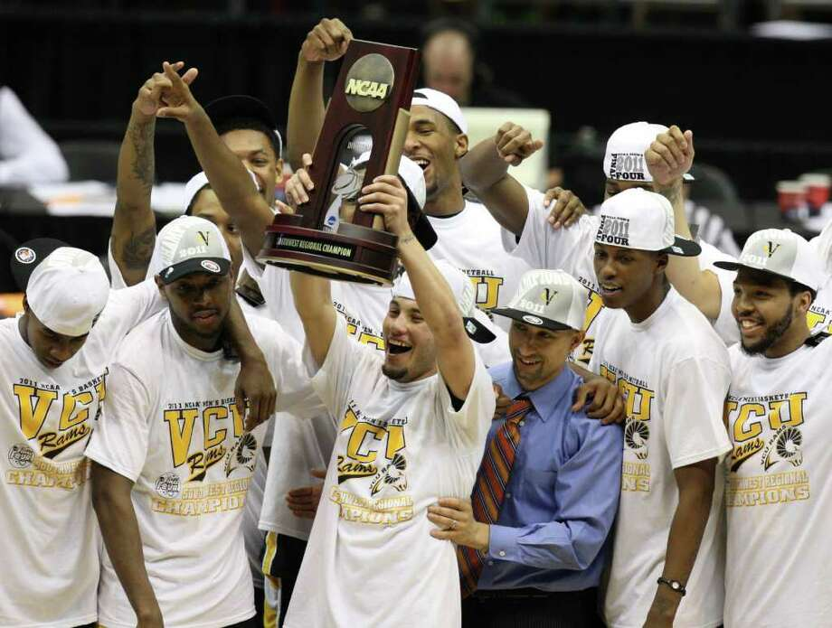Virginia Commonwealth guard Joey Rodriguez (12) holds the NCAA Southwest Regional final trophy in San Antonio, Texas on Sunday, March 27, 2011. VCU won 71-61 over Kansas to advance to the Final Four for the first time in school history.   (Edward A. Ornelas/eaornelas@express-news.net) Photo: Edward A. Ornelas, SAN ANTONIO EXPRESS-NEWS / Edward A. Ornelas