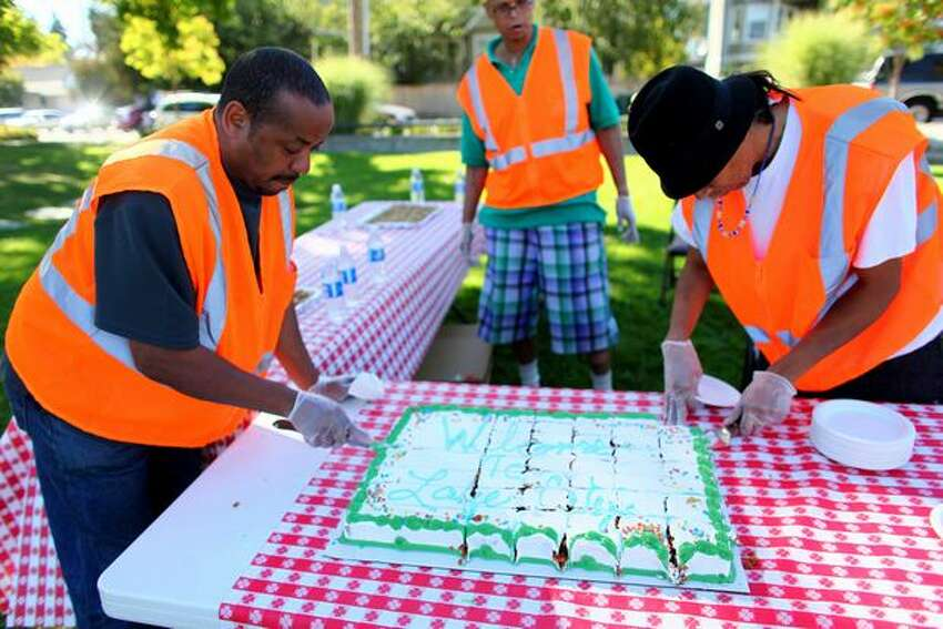 Community Court defendants from left Todd Roberts, Alvin Singer and Sly Sahme cut a cake during a mural celebration at Albert Davis Park in Lake City on Friday September 25, 2009. Community Court defendants painted a mural at the park.