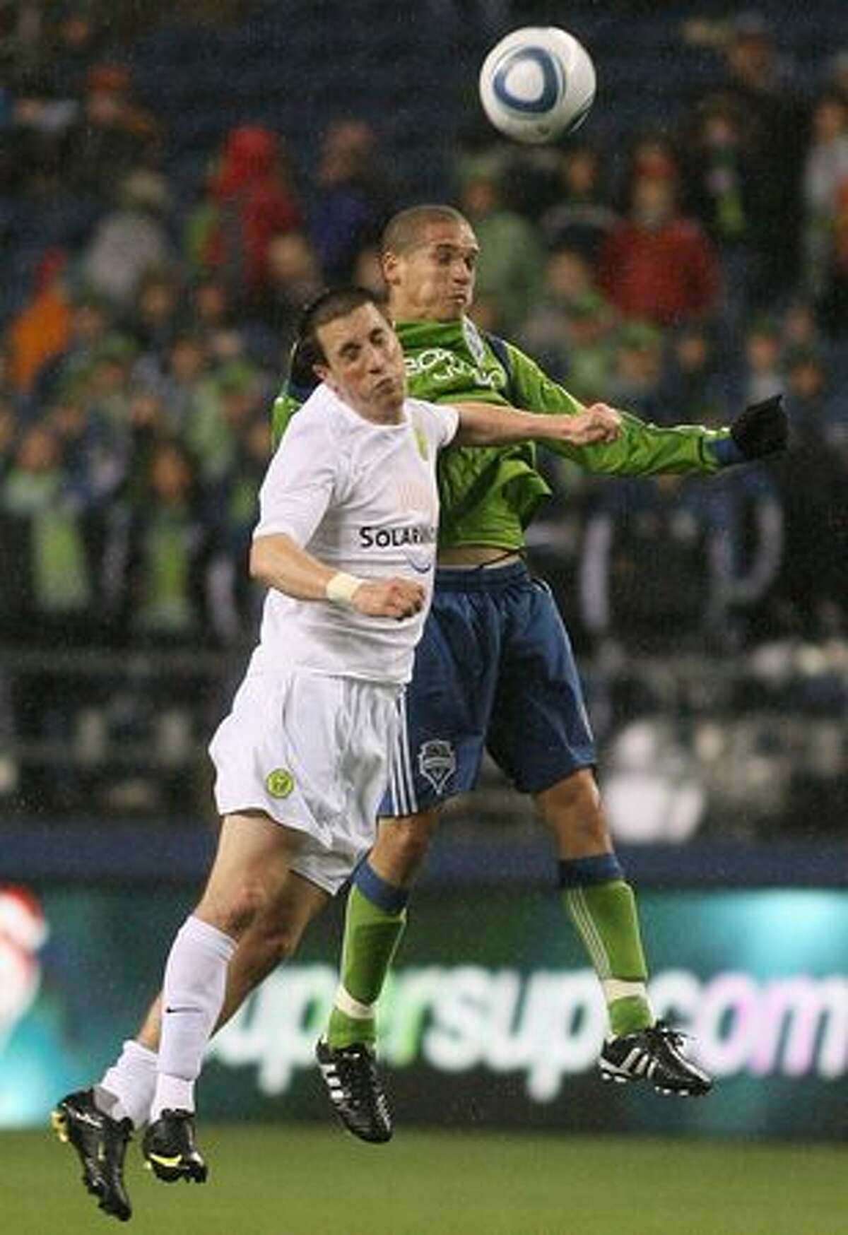 Osvaldo Alonso of the Seattle Sounders goes up for a header against Ryan Pore of the Portland Timbers in the second half of a preseason match on March 11, 2010 at Qwest Field in Seattle.