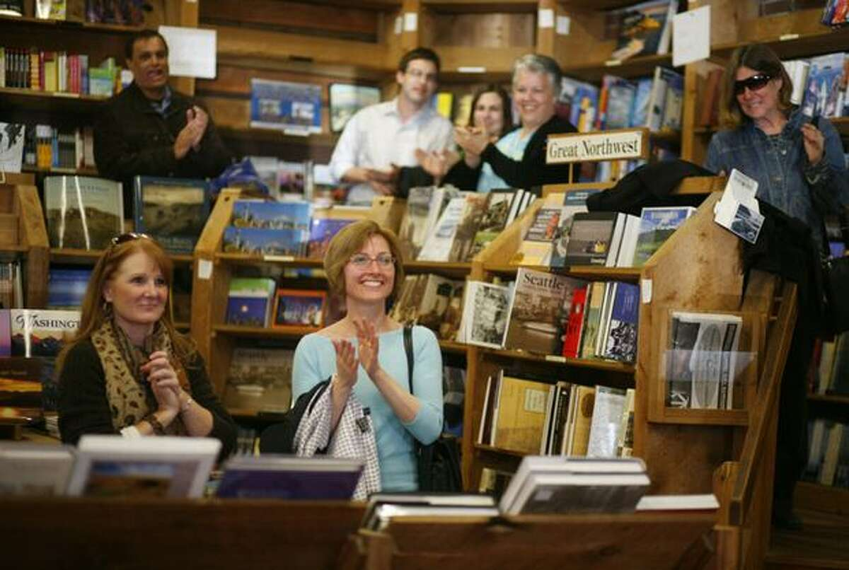 Supporters and workers applaud as the clock strikes 6, closing time at Elliott Bay Book Company's Pioneer Square location on Wednesday March 31, 2010 in Seattle. The legendary bookstore closed its Pioneer Square location on South Main Street Wednesday after 36 years of operation. Owners hope to open its new location at 1521 10th Ave. in Capitol Hill by April 14.