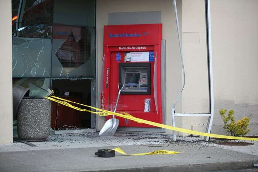 Shattered glass and other debris mark the scene where a man drove his car into the Bank of America branch at Westwood Village in West Seattle. Two people were injured.