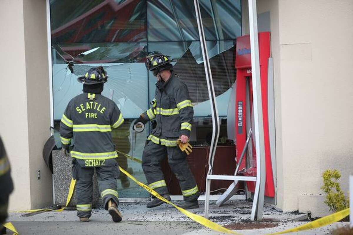 Seattle firefighters clean up glass outside the Westwood Village Bank of America branch after a man drove his car into an outside ATM Thursday at approximately 11:30 a.m. Despite the damage, there were no major injuries. Two people -- a bank teller and a customer who had been near the ATM -- were taken to the hospital with minor injuries.