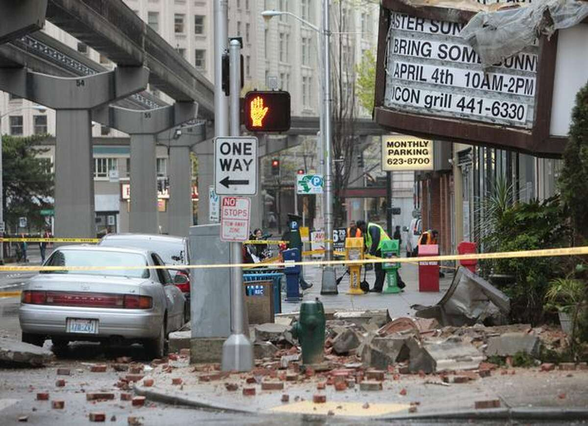 Rubble is strewn across the street and sidewalk after the facade of the Icon Grill building came crashing down onto the street on Friday at the intersection of 5th Avenue and Virgina in Seattle. Three people were injured when bricks came down on them.