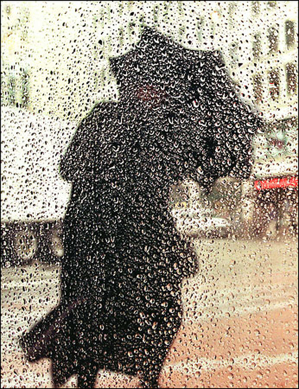 A pedestrian uses an umbrella as a shield against the wind and the rain on the corner of Pike Street and Fourth Avenue in downtown Seattle.
