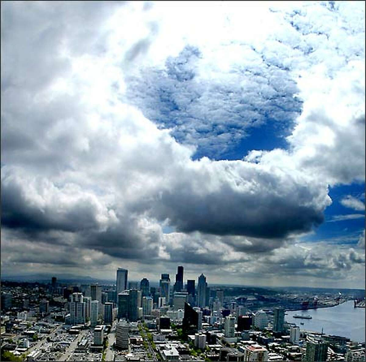 Storm clouds clear for a moment as they pass over the Seattle skyline, allowing the sun to create a brief but dazzling display as viewed from the top of the Space Needle at the Seattle Center.