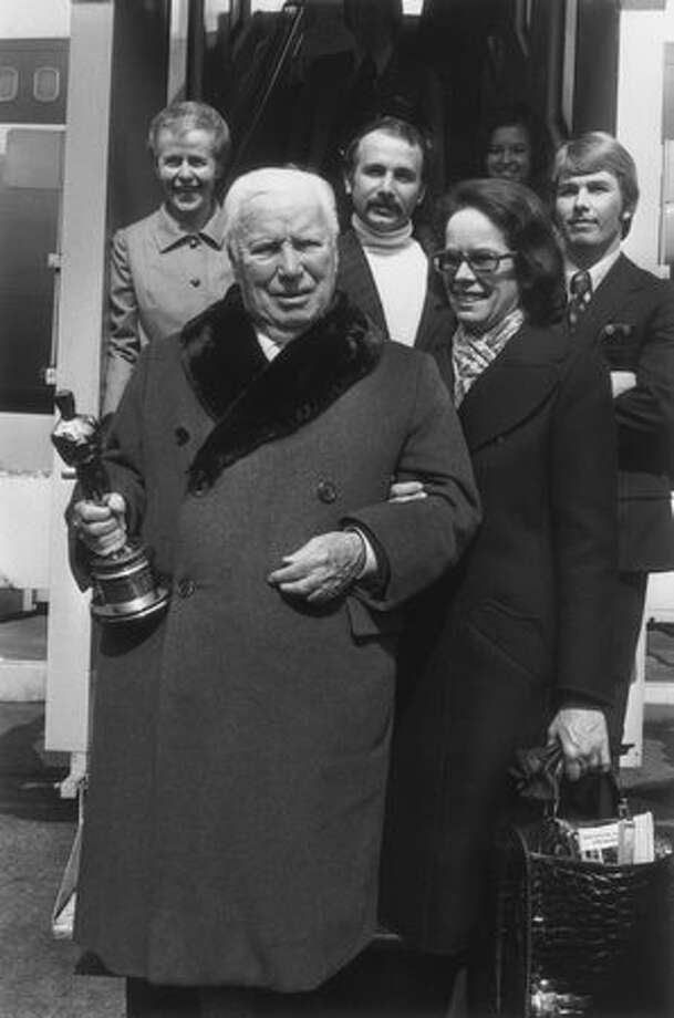 1972: Actor and director Charlie Chaplin (1889 - 1977), holding the honorary Oscar he received in Hollywood, with his wife, Oona, after arriving in London. Photo: Getty Images