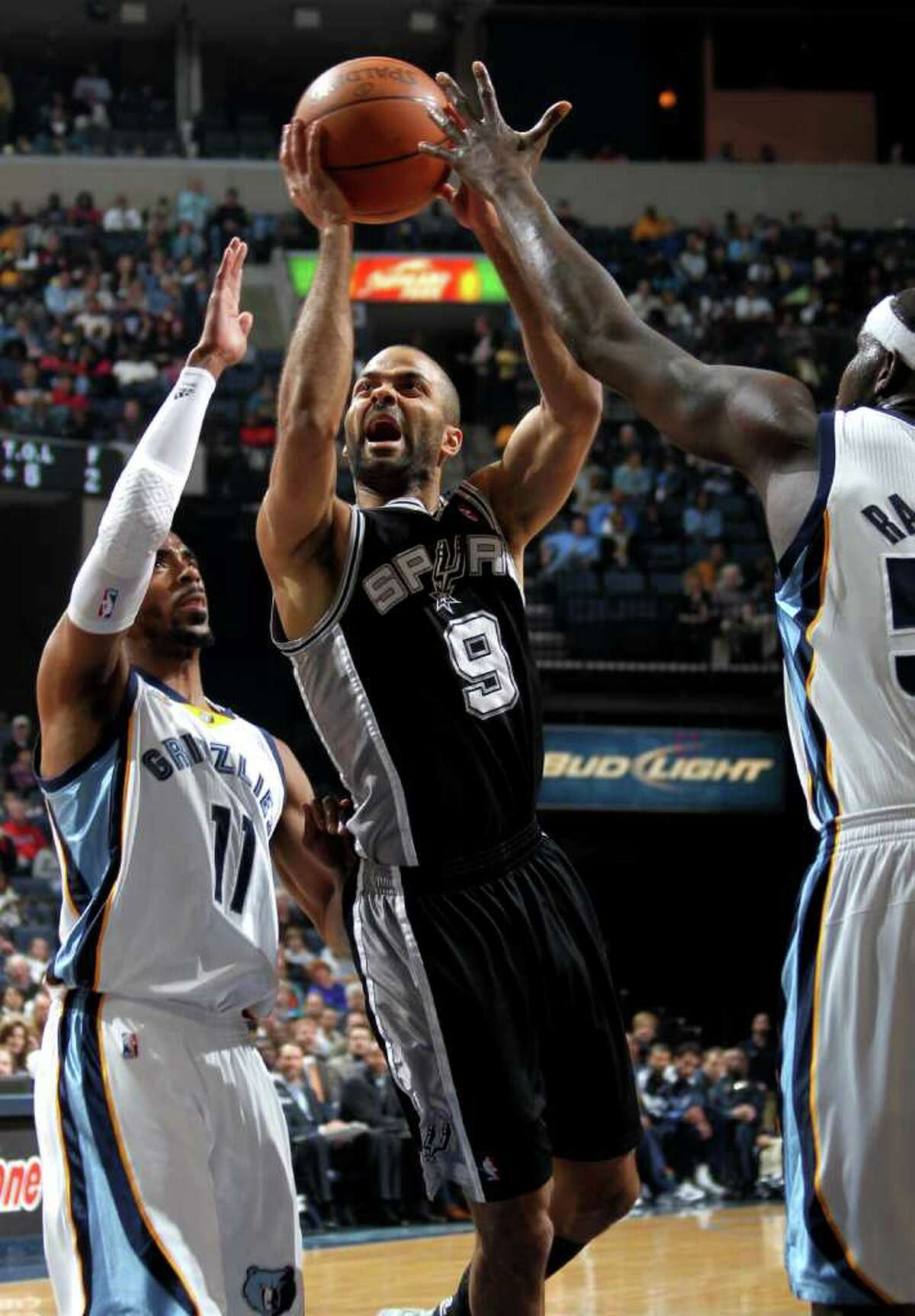 San Antonio Spurs guard Tony Parker, of France, (9), shoots between the defense of Memphis Grizzlies guard Mike Conley (11) and Memphis Grizzlies forward Zach Randolph, right, in the first half of an NBA basketball game Sunday, March 27, 2011, in Memphis, Tenn.