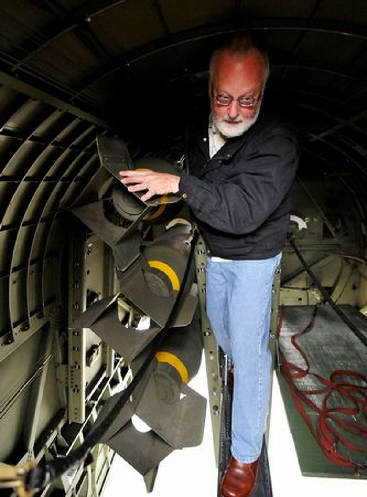 Ron Reisner squeezes through a tight corridor on the B-17 catwalk where bombs are typically stored.