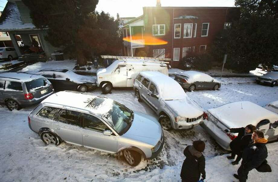 Drivers return to the site of a multiple-car accident on East Boston Street in Seattle's Eastlake neighborhood the morning after snow and ice wreaked havoc on local roads. Photo: Joshua Trujillo, Seattlepi.com / seattlepi.com