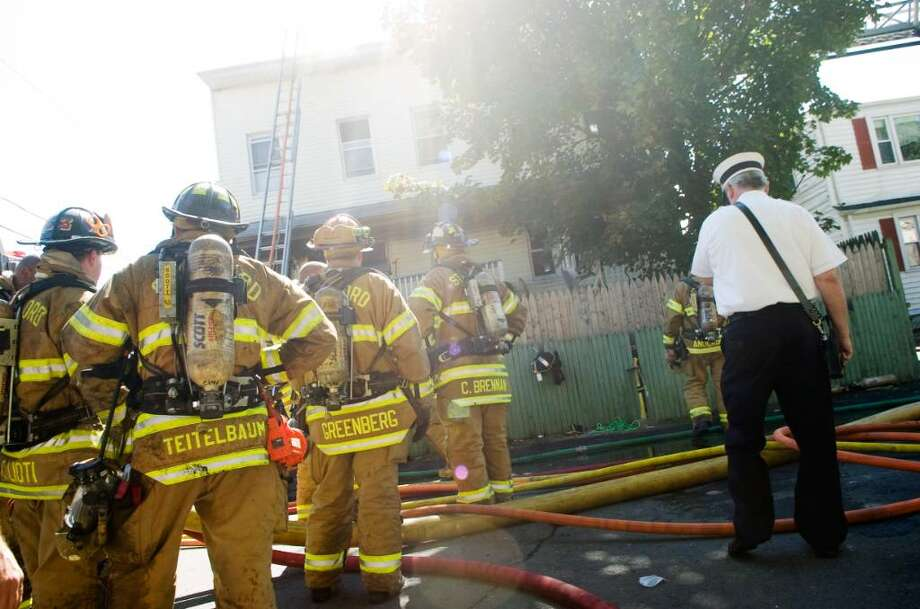 Stamford Fire and Rescue Department firefighters at the scene of a fire at 10 Burr St. in Stamford, Conn. on Monday, Sept. 21, 2009 Photo: Chris Preovolos / Stamford Advocate
