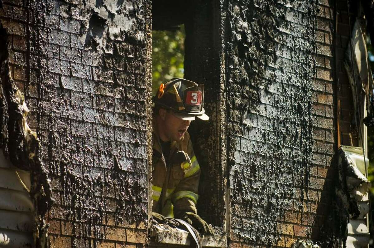 A Stamford Fire and Rescue Department firefighter in a first story window at the scene of a fire at 10 Burr St. in Stamford, Conn. on Monday, Sept. 21, 2009