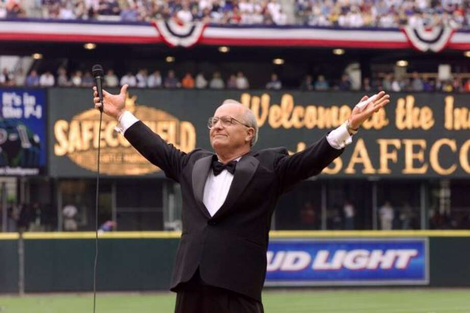 """Dave Niehaus on the mound as he prepares to read a passage from """"Shoeless Joe."""" Niehaus threw out the first pitch at Safeco Field."""