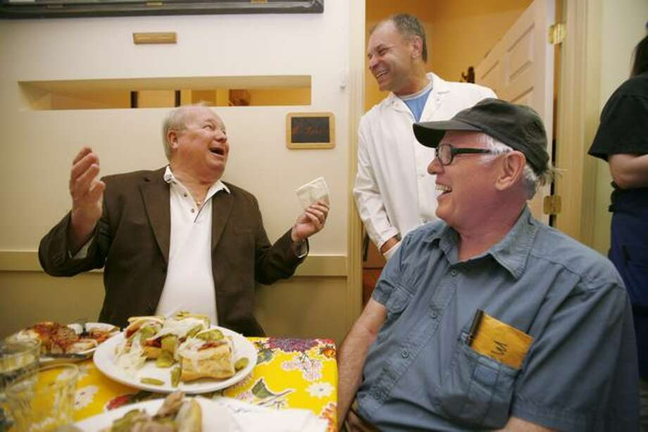 On Thursday, July 24, Dave Niehaus, at left, is overwhelmed by the salami presented to him at Salumi, a Pioneer Square Italian restaurant and purveyor of hand cured meats. At center is Brian D'Amato of Salumi, and at right is Armandino Batali, Principal Salumist. (Paul Joseph Brown/Seattle P-I)