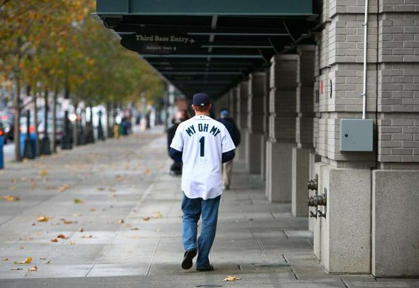 A Seattle Mariner fan wears a jersey with Dave Niehaus' signature standing outside Safeco Field on T