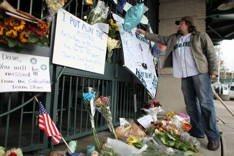 Seattle Mariner fan Brian Bell of Redmond adds to a growing memorial for longtime Mariner broadcaste