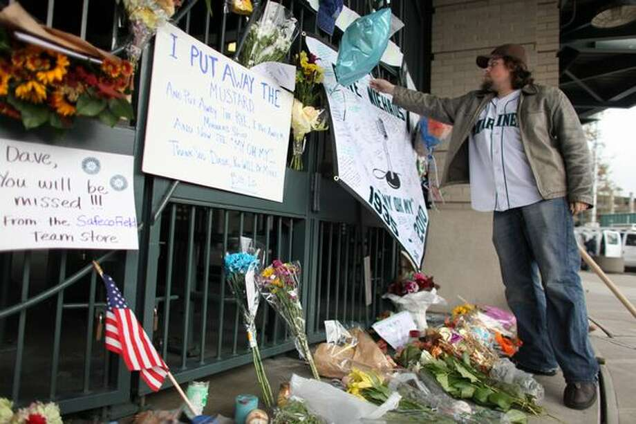 Seattle Mariner fan Brian Bell of Redmond adds to a growing memorial for longtime Mariner broadcaster Dave Niehaus at the gates of Safeco Filed on Thursday. Photo: Joshua Trujillo, Seattlepi.com / seattlepi.com
