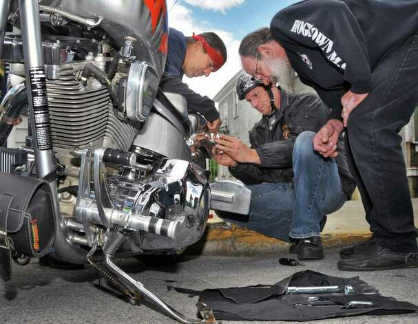 Victor John, right, of Lake George Hardware helps New Jersey bikers Gilly Six, left, and Bob Estelle work on Estelle's chopper June 8 in Lake George Village during the annual Americade.  (John Carl D'Annibale / Times Union) Photo: John Carl D'Annibale / 00009057A