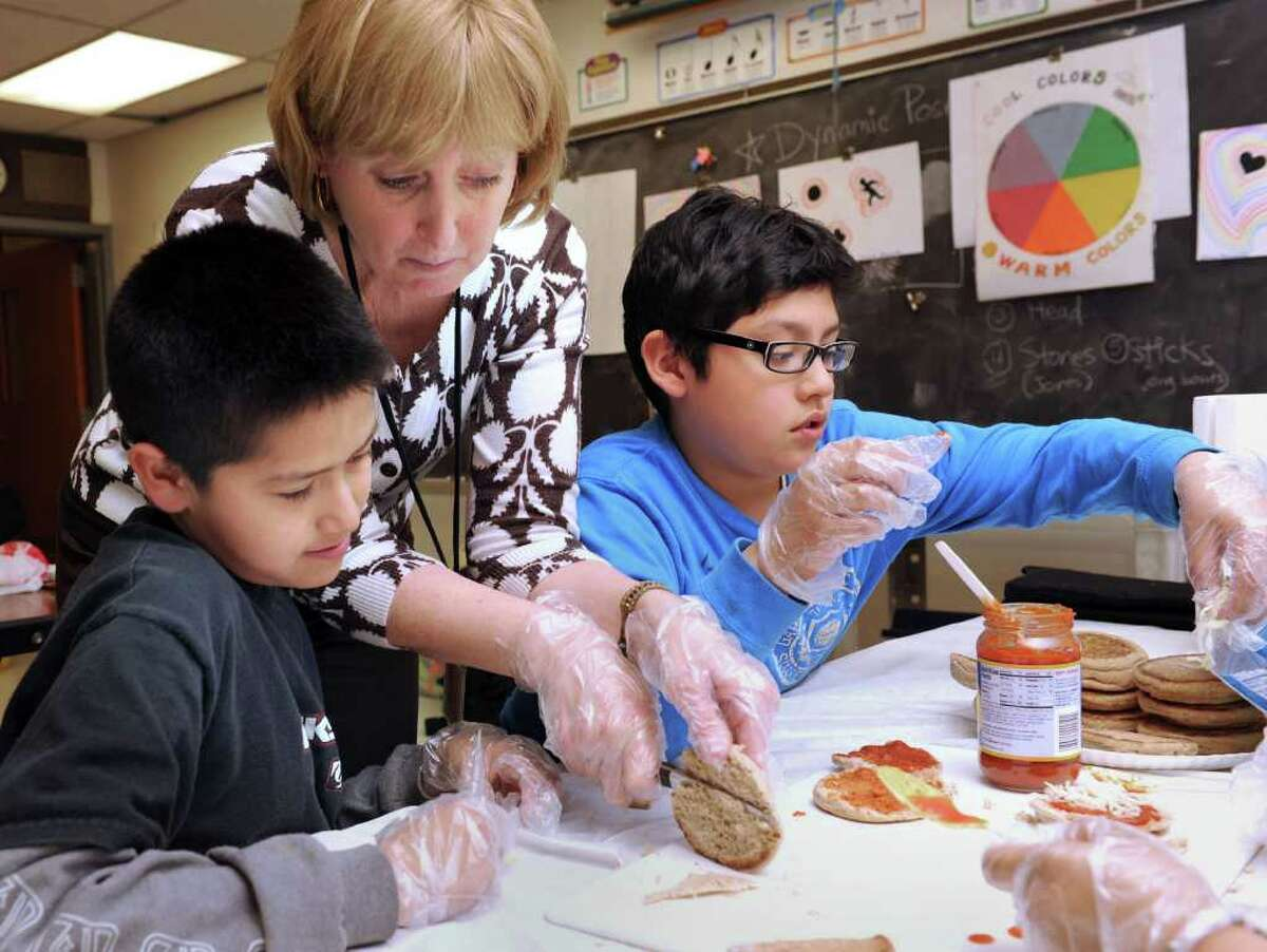 Debby Russell, Youth Developement Specialist with the Family Resource Center at Morris Street School in Danbury, helps Michael Duran, left, and Adan Mendoza, 10, make English muffin pizzas Monday. The kids are part of the 5th Grade Upper EL Club which focuses on leadership training. Photo taken Monday, March 28, 2011.