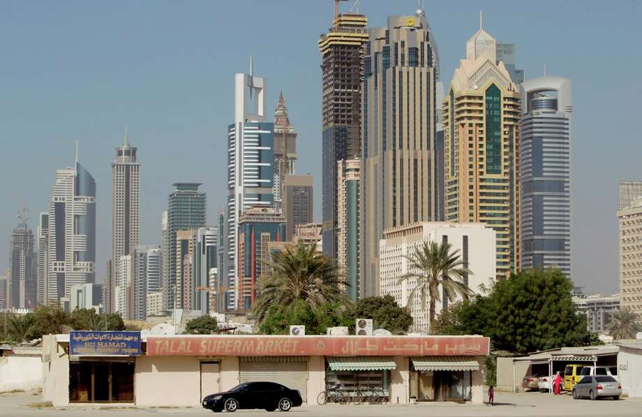 With the Sheikh Zayed highway modern towers in the background, a car passes by in front of Talal supermarket in the old part of the Al Wasl district of Dubai. Photo: AP Photo/Kamran Jebreili