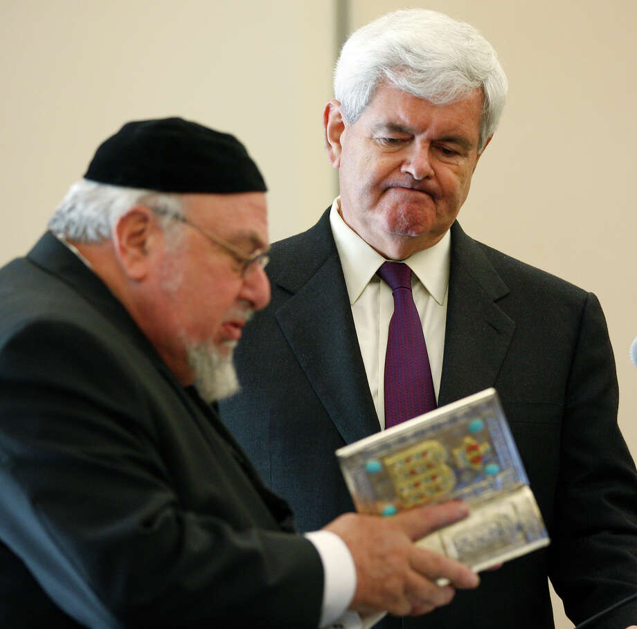 Rabbi Aryeh Scheinberg (left) presents former Speaker of the House Newt Gingrich with a Bible on being honored with the Keeping of the Faith Award by Bridges & Pathways. Photo: Jerry Lara/glara@express-news.net / SAN ANTONIO EXPRESS-NEWS