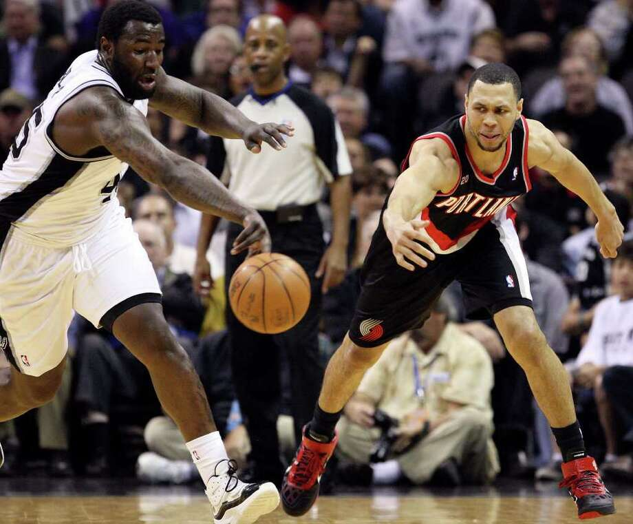 FOR SPORTS - Spurs' DeJuan Blair and Trail Blazers' Brandon Roy grab for a loose ball during first half action Monday March 28, 2011 at the AT&T Center.  (PHOTO BY EDWARD A. ORNELAS/eaornelas@express-news.net) / SAN ANTONIO EXPRESS-NEWS (NFS)