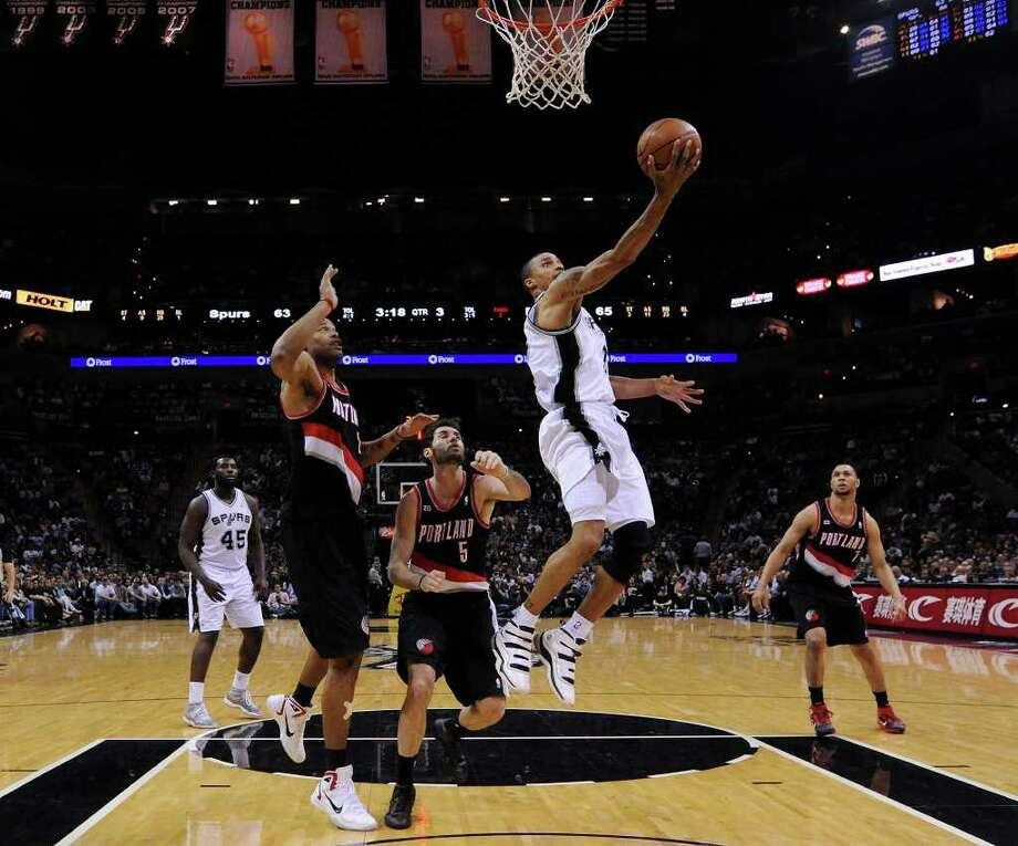 FOR SPORTS - Spurs' George Hill shoots between Trail Blazers' Marcus Camby, Trail Blazers' Rudy Fernandez and Trail Blazers' Brandon Roay during second half action Monday March 28, 2011 at the AT&T Center.  The Trail Blazers won 100-92. (PHOTO BY EDWARD A. ORNELAS/eaornelas@express-news.net) / SAN ANTONIO EXPRESS-NEWS (NFS)