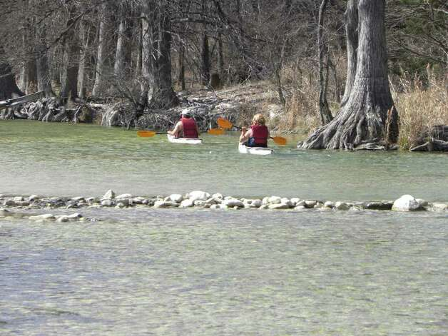 A couple kayaks on the Guadalupe River in Guadalupe River State Park. Though most families come to the park for the rivier, it also  has 5.3 miles of hiking trails plus the Honey Creek State Natural Area, which offers a guided hike. Photo credit: Tara Dooley / DirectToArchive