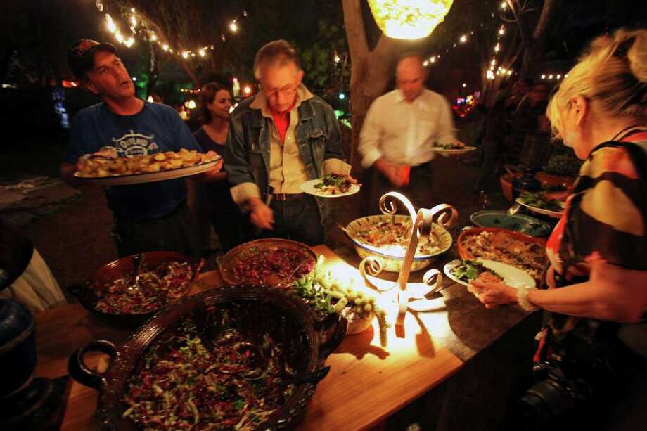 John Fahle (left) brings out replenishments for The Long Table of Love, a fundraiser for Casa Chuck, an artist residency at the house of the late artist Chuck Ramirez. Photo: TOM REEL, SAN ANTONIO EXPRESS-NEWS / © 2011 San Antonio Express-News