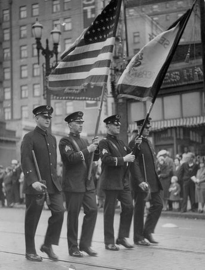 Police officers bear flags during a procession. Photo: P-I File